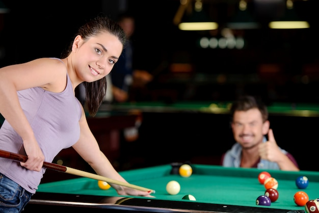 The girl plays billiards and poses for the camera.