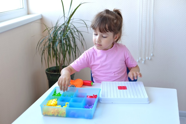 The girl plays the children's educational constructor puzzle with a screwdriver, a screwdriver and shurukas with multi-colored geometric shapes. creative preschooler development concept.