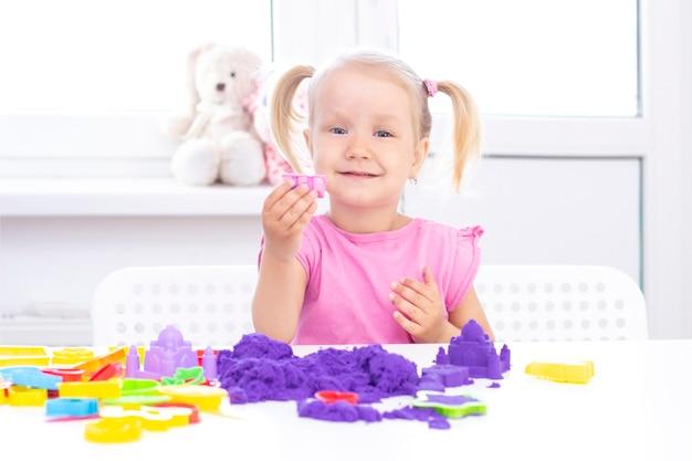 Girl plays kinetic sand in quarantine