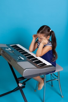 Girl plays music with her elbows on an electronic synthesizer