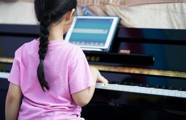 女の子はオンライン学習タブレットでピアノを弾きます