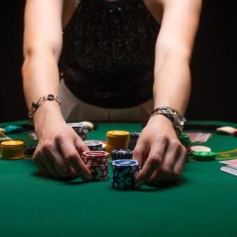 Девушка играет в покер и повышает ставки с фишками
