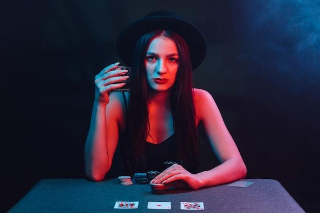 소녀는 카지노에서 카드와 칩이 있는 테이블에서 포커를 합니다. 도박 개념