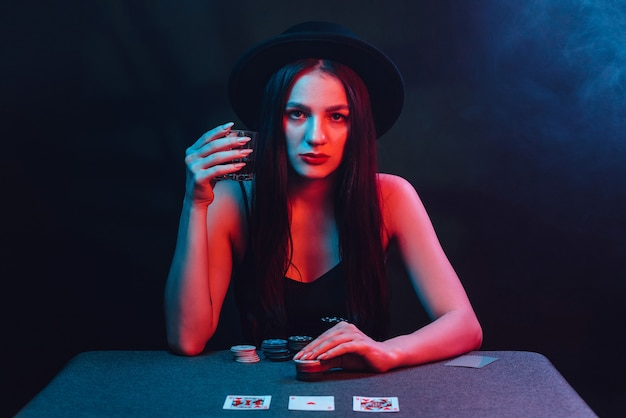 Girl plays poker at a table with cards and chips in a casino. gambling concept