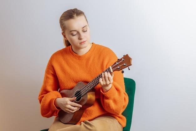 A girl plays a ukulele on a light background