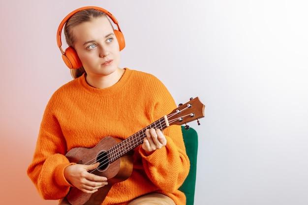 A girl plays the ukulele