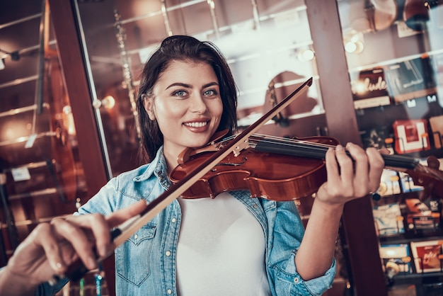 Girl plays violin in store of musical instruments.