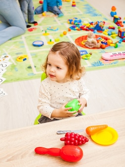 Girl plays with children's housewares and artificial fruit at the table. kitchen equipment