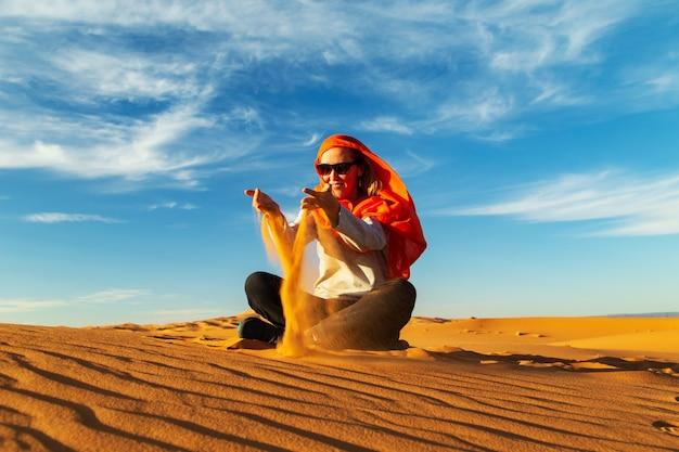 女の子はサハラ砂漠で砂で遊ぶ。 erg chebbi、merzouga、モロッコ。