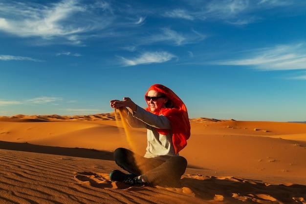 Девушка играет с песком в пустыне сахара. эрг шебби, мерзуга, марокко.