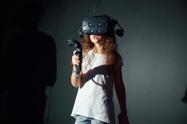 Девушка играет с очками виртуальной реальности, держит в руках контроллер