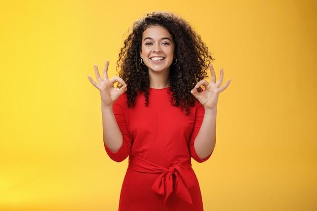 女の子はすべてが計画通りに進んで大丈夫だと喜んだ。赤いドレスを着た巻き毛の幸せで楽しいカリスマ的な女性は、承認などで大丈夫なジェスチャーを示し、黄色の壁の上の良い仕事に満足しています。