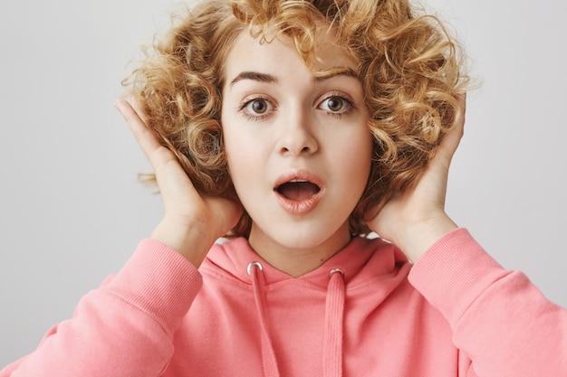 カーリーヘアスタイルで作られた素晴らしい新しいスタイリッシュなヘアカットに満足している女の子