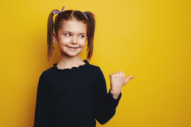 Девушка, указывая в сторону, демонстрирует промо справа, представляет промо над желтым