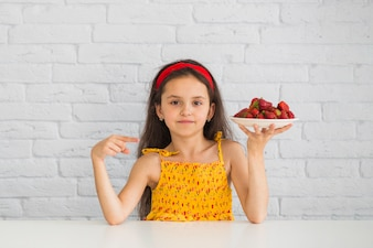 Girl pointing at plate with fresh organic strawberry