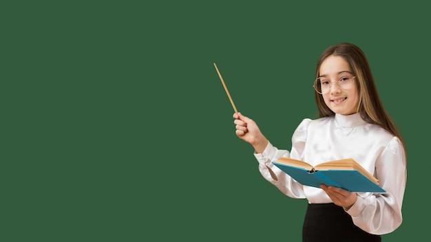 Girl pointing at blackboard