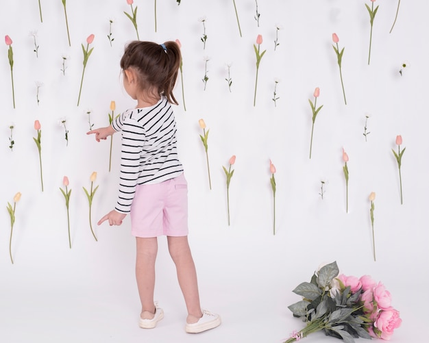 Girl pointing at flowers