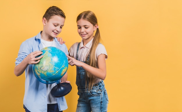 Girl pointing on globe hold by his friend against yellow background