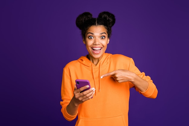 Girl pointing at her telephone in orange sweater smiling
