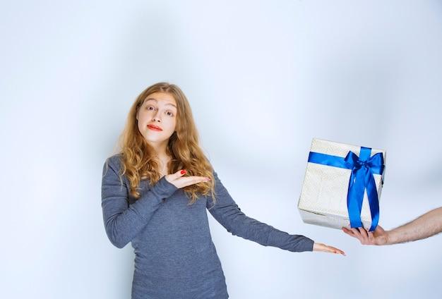 Ragazza che indica un contenitore di regalo blu bianco offerto a lei.