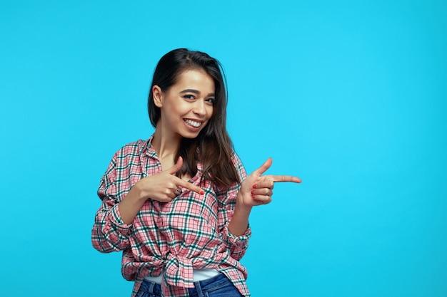 Девушка указывает обеими руками на правое пустое пространство, стоящее на синем фоне