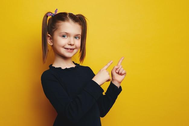 Девушка показывает обеими руками на правое пустое пространство, стоящее на желтом фоне