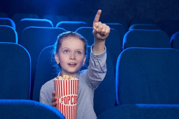 영화관에서 화면에 손가락으로 가리키는 소녀.