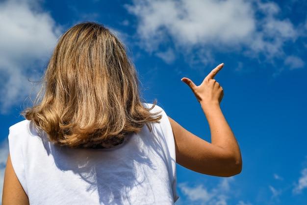 Девушка указывает пальцем на небо. вид сзади. далеко ждать силуэт направление путь выбрать ландшафтный курорт экскурсионную концепцию.