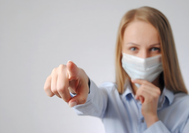 Девушка показывает на вас пальцем в медицинской маске