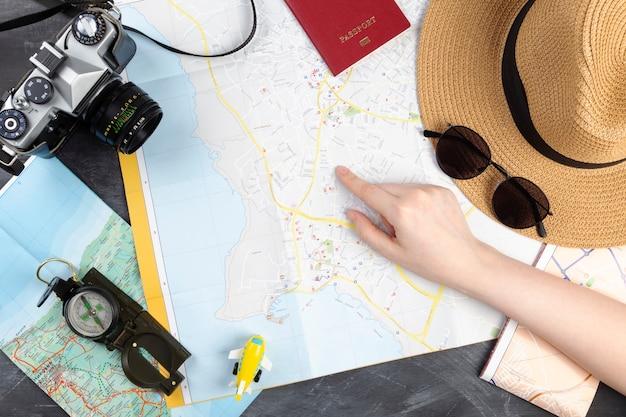 Девушка указывает пальцем на точку на карте. туристическое планирование с картой.