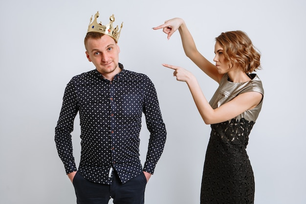 The girl points her fingers at the crown, which is put on the guy's head.