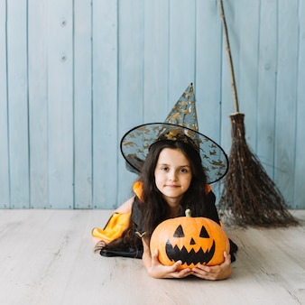 Girl in pointy hat and broom holding pumpkin