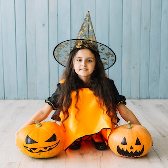 Girl in pointy hat sitting on floor with pumpkins