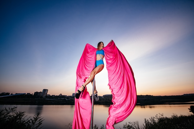 Girl pole dancer performs an element on the pole with wings and beautiful flying, flowing fabric