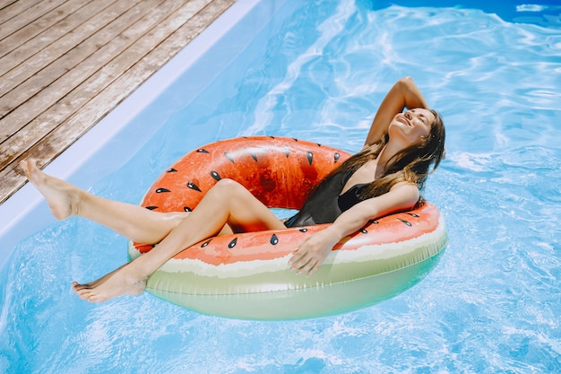 Girl in a pool. woman in a stylish swimsuits. lady on a summer vacation