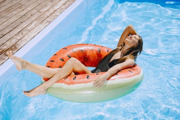 Ragazza in una piscina. donna in un costume da bagno alla moda. signora in vacanza estiva