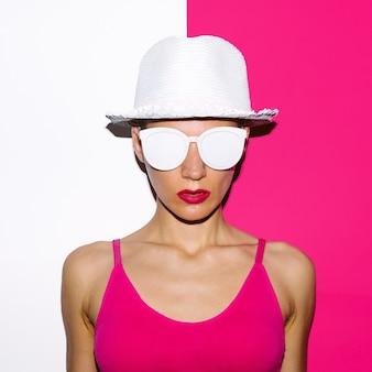 Девушка в стиле поп-арт в пляжной шляпе и солнцезащитных очках