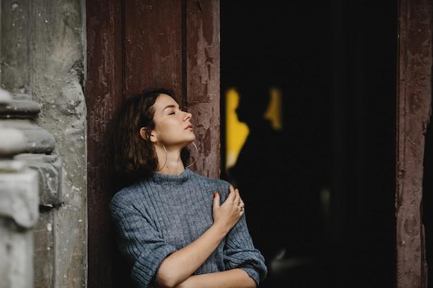 Портрет девушки возле двери старого здания и на заднем плане силуэт мужчины