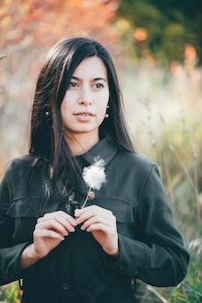 背景のボケ味の秋の花を持つ少女の肖像画。