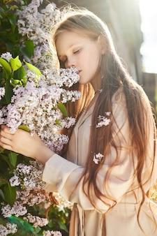 소녀는 봄에 라일락 덤불에서 포즈를 취합니다. 태양 빛에 꽃에서 아이의 낭만적인 초상화