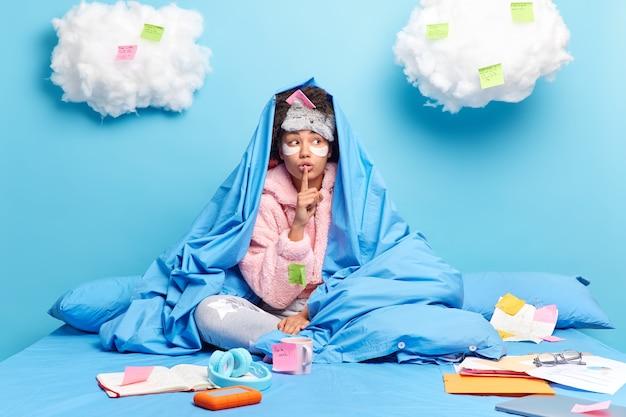 소녀는 멀리 많은 서류와 스티커 메모로 둘러싸인 가정 연구에서 편안한 침대에 포즈를 취하고 파란색에 고립 된 비밀 제스처를 만듭니다