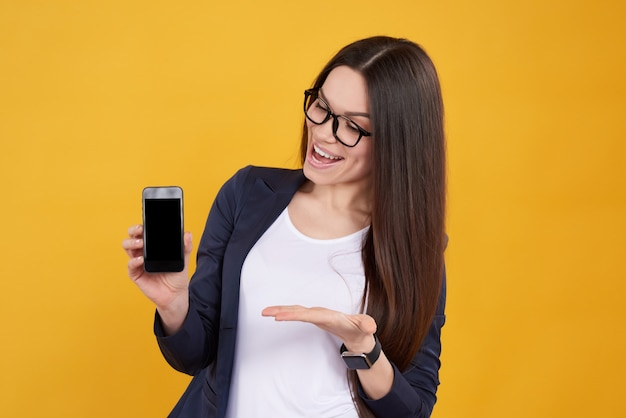 Girl poses with black phone, thumbs up on yellow background.