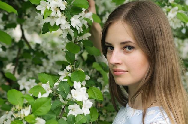 花の咲く木々を背景にポーズをとる少女