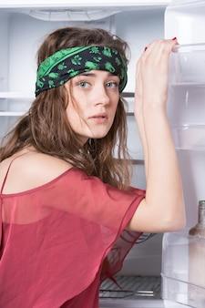 Девушка позирует у открытой двери холодильника с пустыми полками на белом фоне. концепция кухонной мебели и бытовой техники.