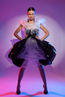 Girl posing in a dress made of plastic film