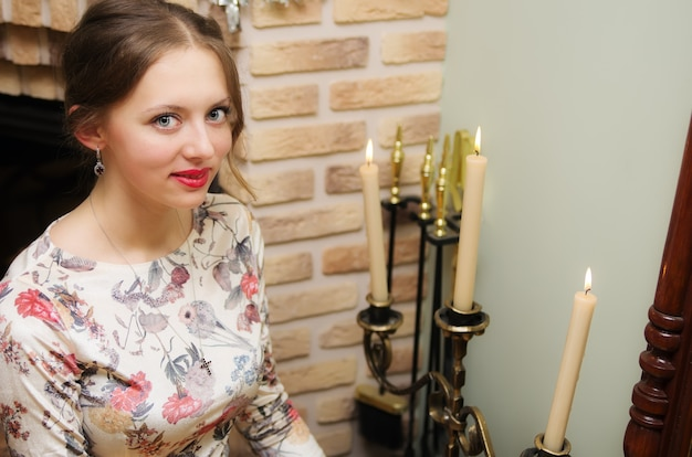 촛불 샹들리에 근처에 앉아 아름다운 드레스를 입고 포즈를 취하는 소녀