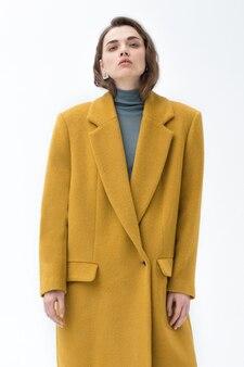 黄色のコートと青いタートルネックでポーズをとる女の子