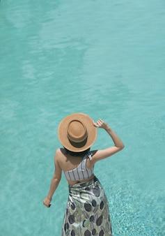 Девушка позирует возле бассейна в модном купальнике с отражением в бассейне на заднем плане / летняя активность