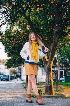 オレンジの木の近くの街の通りでポーズをとる少女。都会的なスタイル。カメラを見てください。