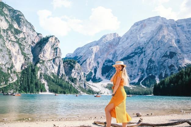 アルプスの風光明媚な山の湖のほとりでポーズをとる少女。ドロミテ、イタリア、ヨーロッパのブラーイエス湖の眺め。